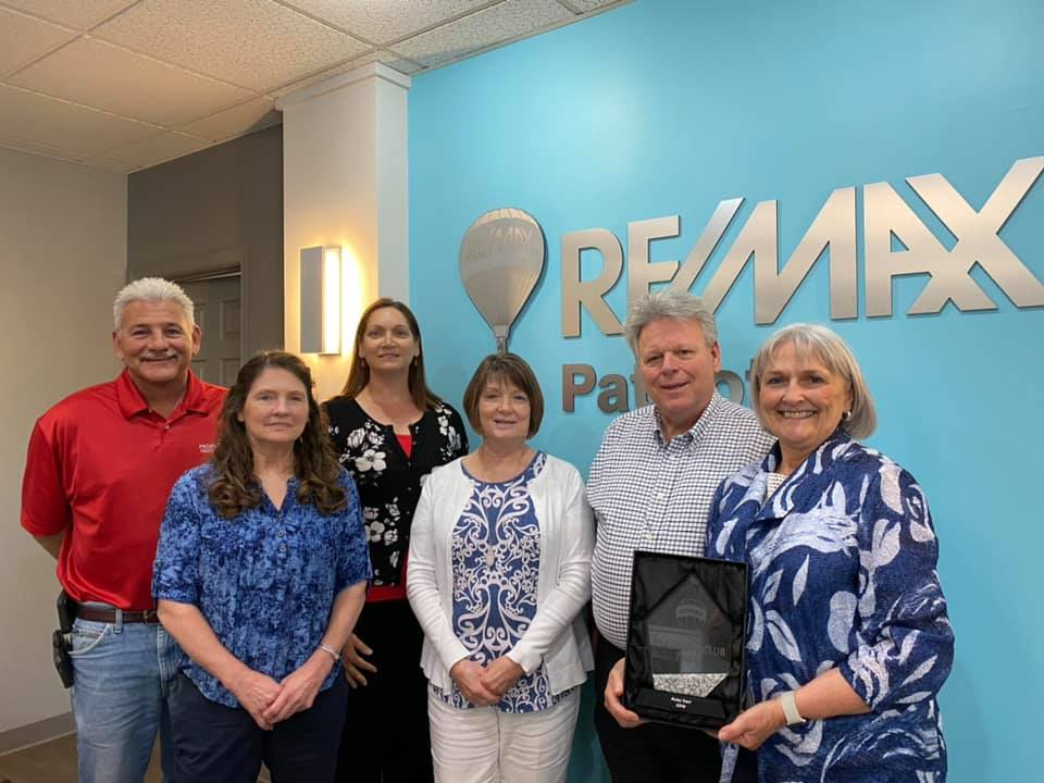 The real estate agents of the Ruby Darr team standing together in the RE/MAX Patriots office and holding the Platinum award